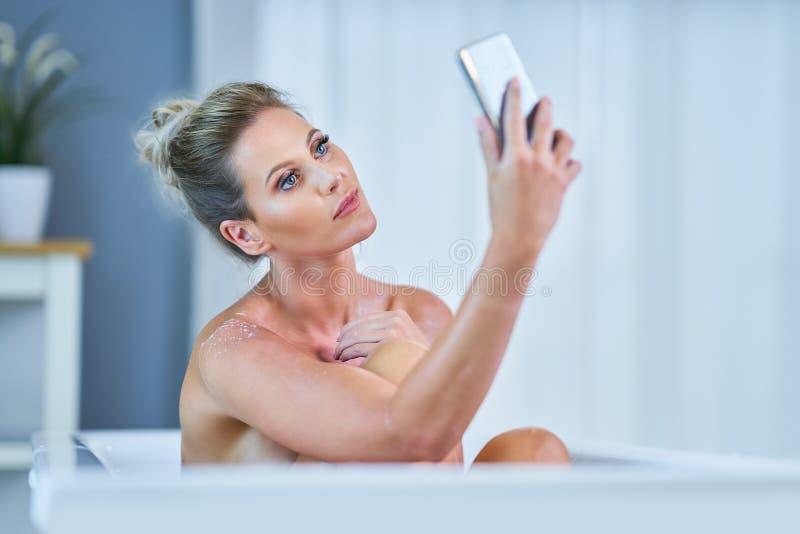 Close-upportret van een jonge vrouw die in bathtube ontspannen stock fotografie