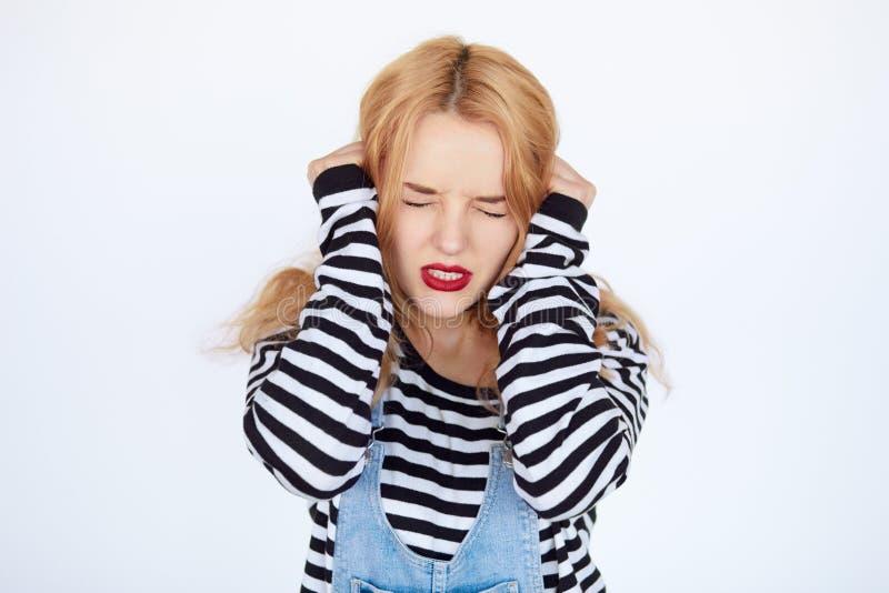 Close-upportret van een jonge vrouw die hoofdpijn hebben royalty-vrije stock foto