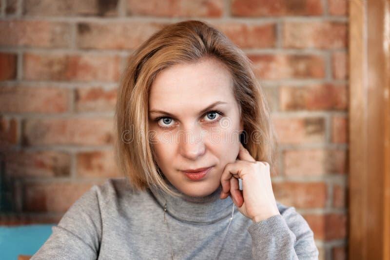 Close-upportret van een jonge vrouw die recht de camera bekijken tegen vage achtergrond stock foto's