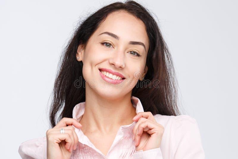 Close-upportret van een jonge zeer mooie vrouw met een charmante toothy glimlach, een zwart haar en bruine ogen op een witte acht stock fotografie