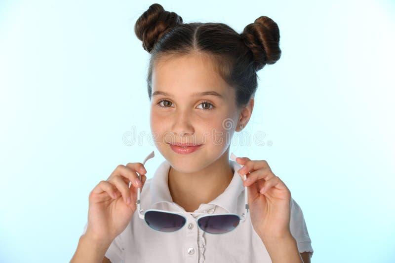 Close-upportret van een klein meisje 12 jaar oud in een witte blouse met zonnebril stock foto