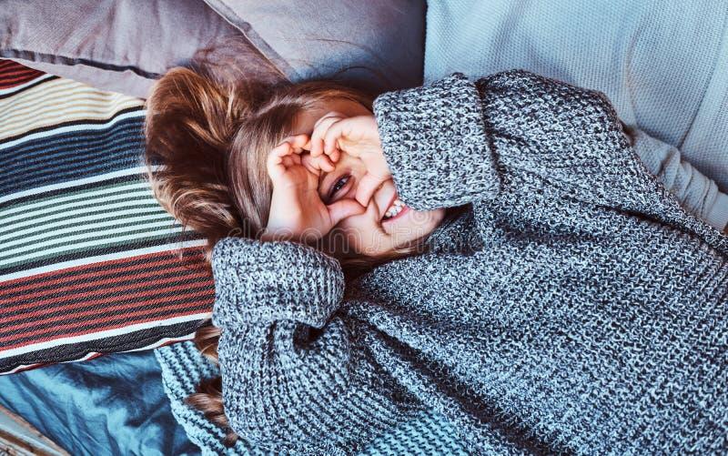 Close-upportret van een klein meisje in warme sweater die op bed liggen stock foto