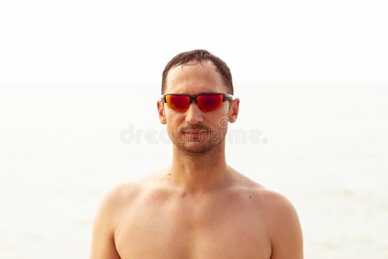 Close-upportret van een knappe jonge volwassen ongeschoren mens in rode modieuze zonnebril tegen overzees royalty-vrije stock afbeelding