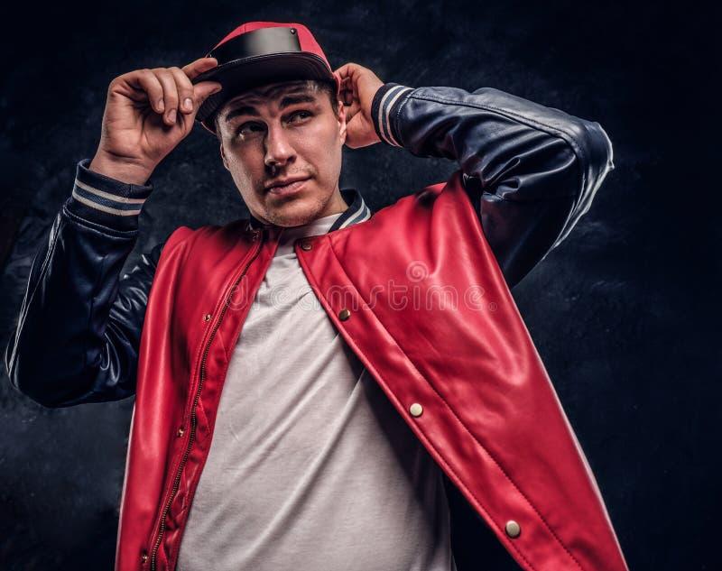 Close-upportret van een knappe mens gekleed in een hiphopstijl Studiofoto tegen een donkere muur royalty-vrije stock afbeelding