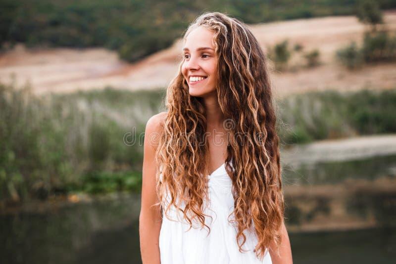Close-upportret van een mooi glimlachend blondemeisje met natuurlijke krullen royalty-vrije stock afbeelding