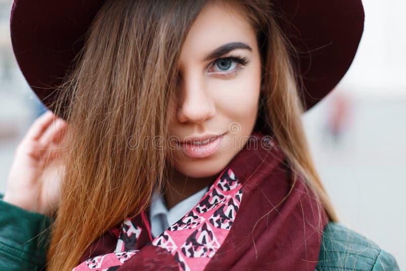 Close-upportret van een mooi jong meisje in een hoed van Bourgondië stock foto's