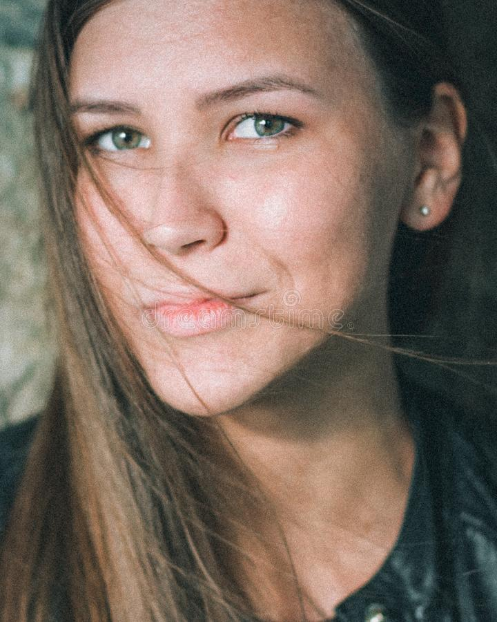 Close-upportret van een mooi Kaukasisch meisje met lang blond stromend haar Een jonge vrouw kijkt recht in stock foto