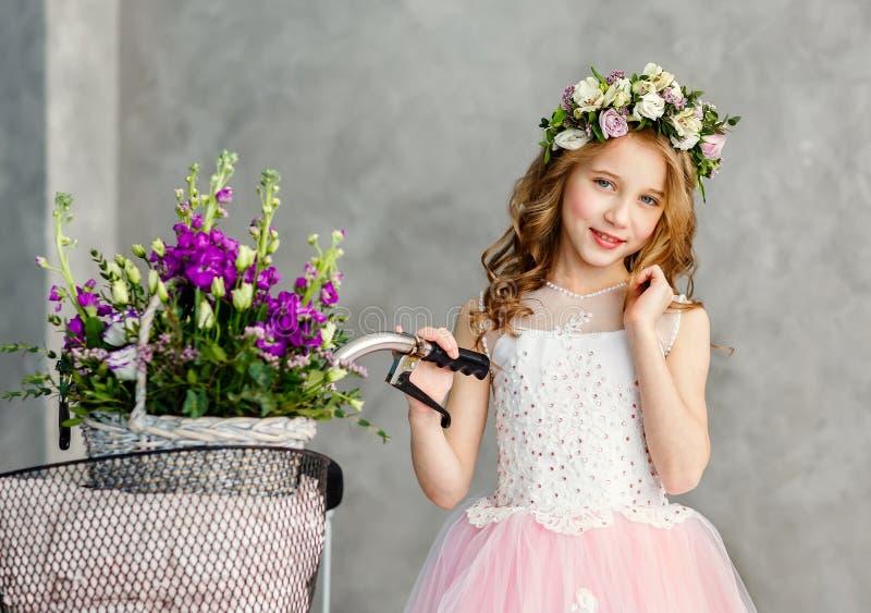 Close-upportret van een mooi leuk meisje in een kroon van verse bloemen op haar hoofd en een mand van de mooie lente royalty-vrije stock afbeelding