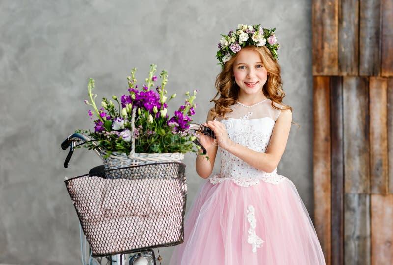 Close-upportret van een mooi leuk meisje in een kroon van verse bloemen op haar hoofd en een mand van de mooie lente stock fotografie