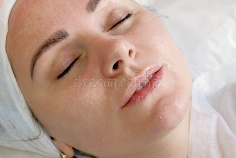 Close-upportret van een mooi vrouwelijk gezicht met schone bevochtigde huid Transparant gel op de lippen van vrouwen Ontspannen m stock afbeeldingen