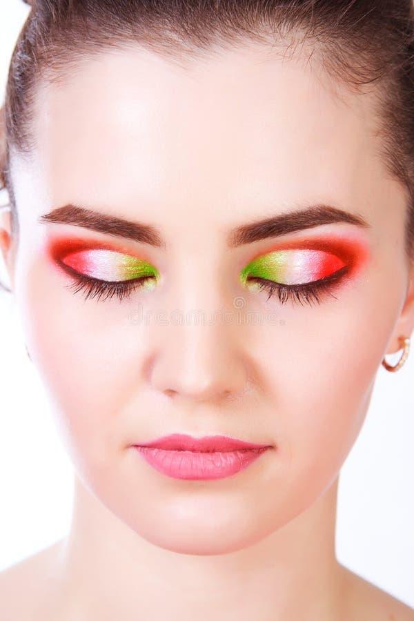 Close-upportret van een mooie jonge vrouw met een heldere make-up stock afbeelding