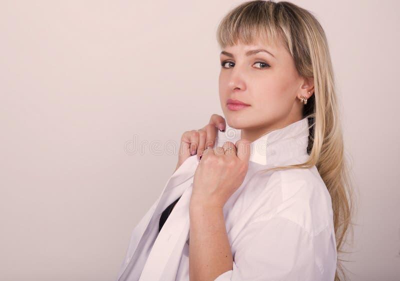 Close-upportret van een mooie sexy vrouw in een wit overhemd over zijn naakt lichaam, op een donkere achtergrond stock afbeelding
