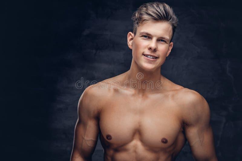 Close-upportret van een sexy shirtless jonge mensenmodel met een spierlichaam en het modieuze kapsel stellen bij een studio stock foto