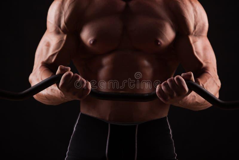 Close-upportret van een spiermensentraining met barbell bij gymnastiek stock afbeelding