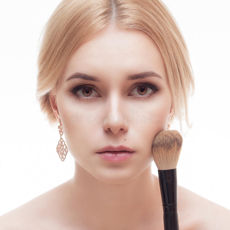 Close-upportret van een vrouw die droge kosmetische toon- stichting op het gezicht toepassen royalty-vrije stock afbeeldingen