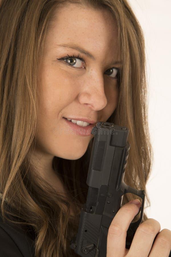 Close-upportret van een vrouw die een pistool met een grijnslach op hij houden royalty-vrije stock foto's