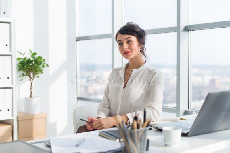 Close-upportret van een vrouwenzitting in modern zolderbureau, het glimlachen, die camera bekijken Jonge zekere vrouwelijke zaken royalty-vrije stock afbeelding