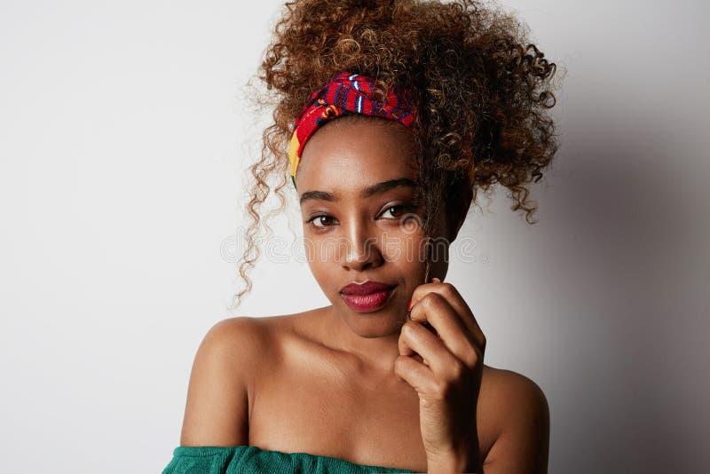 Close-upportret van een zeker jong Amerikaans Afrikaans meisje met lang krullend haar die zich alleen tegen een wit bevinden royalty-vrije stock fotografie