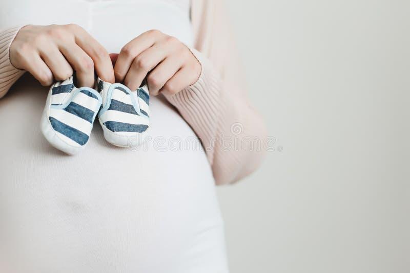 Close-upportret van een zwangere vrouw die een babybuiten houden die op een witte achtergrond worden ge?soleerd stock foto's