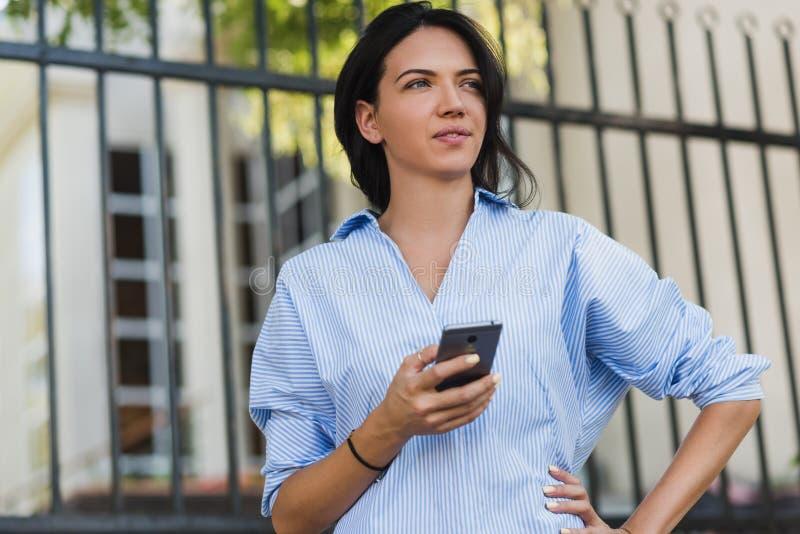 Close-upportret van ernstige aantrekkelijke vrouw met mobiele telefoon weg en wachtende vriend die op de stadsstraat kijken Jong  stock fotografie