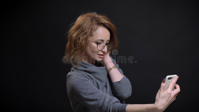 Close-upportret van extravagant rood haired wijfje op middelbare leeftijd in glazen die selfies op de telefoon nemen en vooraan s stock fotografie