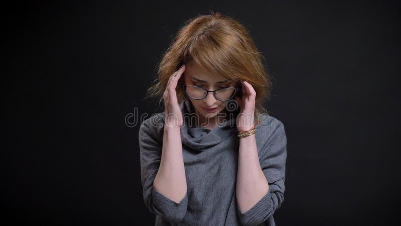 Close-upportret van extravagant roodharigewijfje op middelbare leeftijd in glazen die een hoofdpijn hebben en voor worden vermoei royalty-vrije stock fotografie