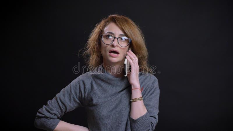 Close-upportret van extravagant roodharigewijfje op middelbare leeftijd in glazen die een toevallig gesprek op de telefoon vooraa royalty-vrije stock foto