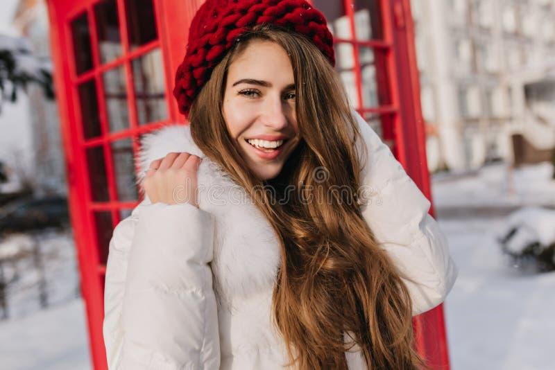Close-upportret van gelukkig meisje met het glanzende bruine haar stellen naast rode vraag-doos Openluchtfoto van het overweldige stock foto