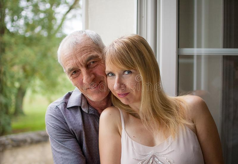 Close-upportret van Gelukkig Paar met Leeftijdsverschil die dichtbij het Venster in Hun Huis tijdens de Zomer Hete Dag koesteren stock afbeelding