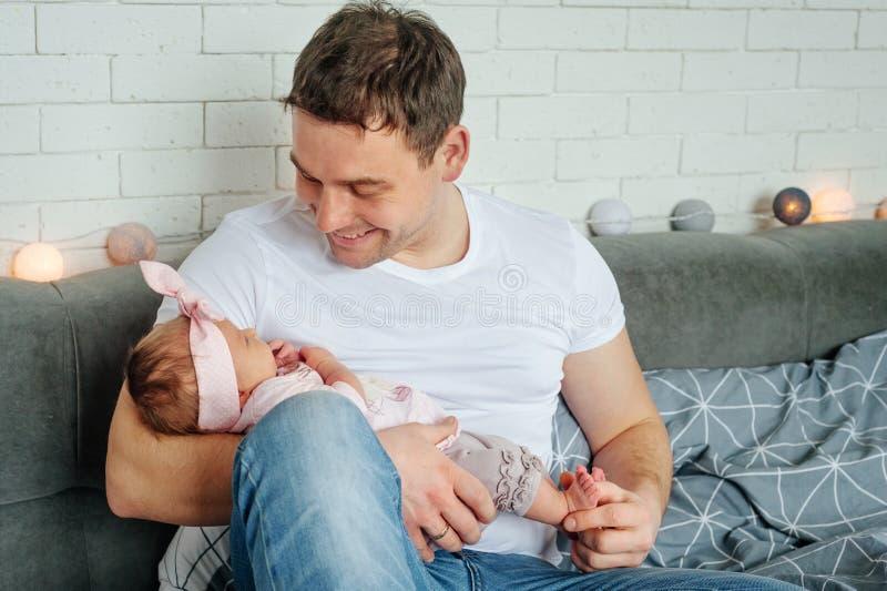 Close-upportret van gelukkige jonge vader die en zijn zoet aanbiddelijk pasgeboren kind koesteren kussen Gelukkig familieconcept stock afbeeldingen