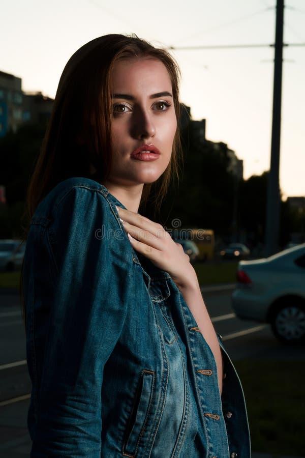 Close-upportret van glamour het donkerbruine vrouw stellen op straat i stock afbeelding