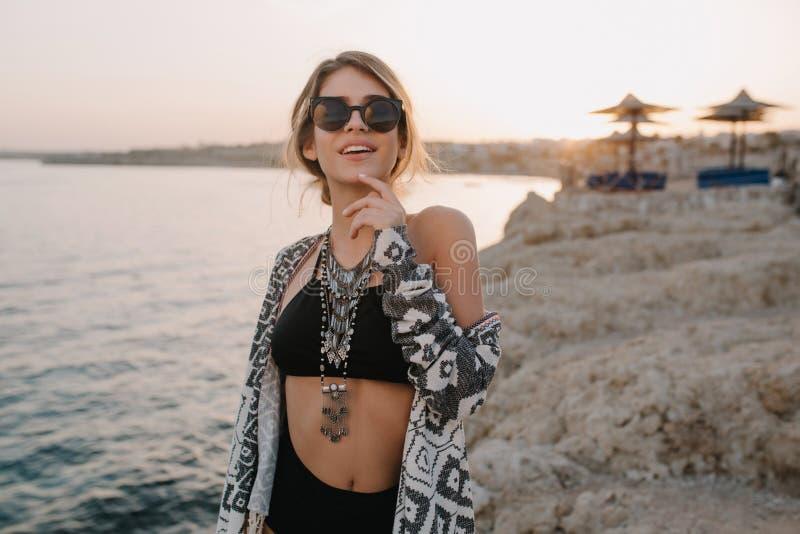 Close-upportret van glimlachend jong meisje op strand, zonsondergangtijd Het dragen van in zwart zwempak, bikini, modieuze zonneb stock foto