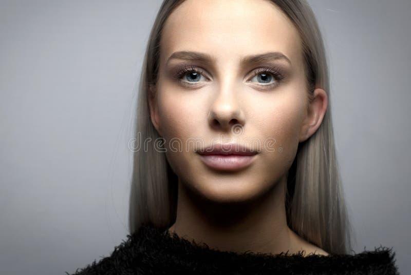 Close-upportret van glimlachende blondevrouw met woedejasje royalty-vrije stock fotografie