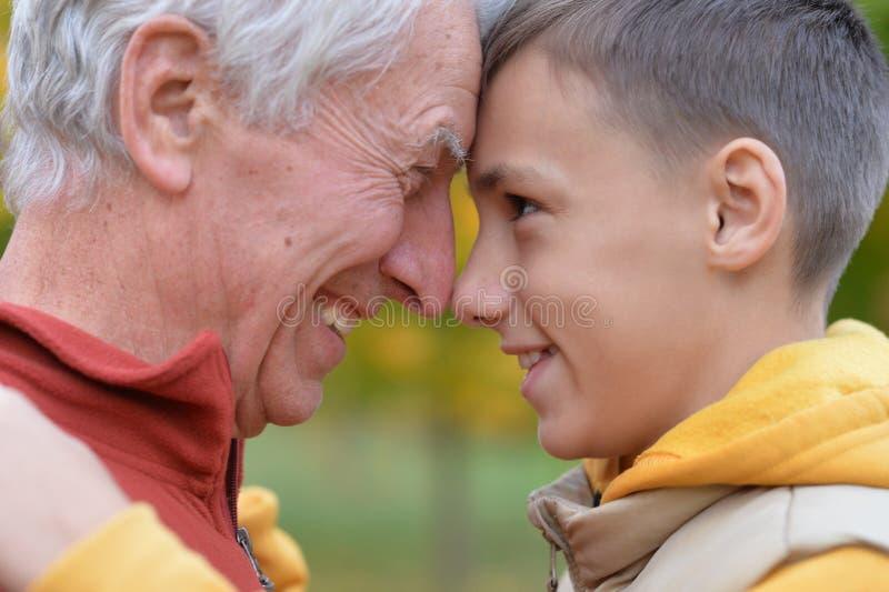 Close-upportret van glimlachende grootvader en kleinzoon royalty-vrije stock afbeeldingen