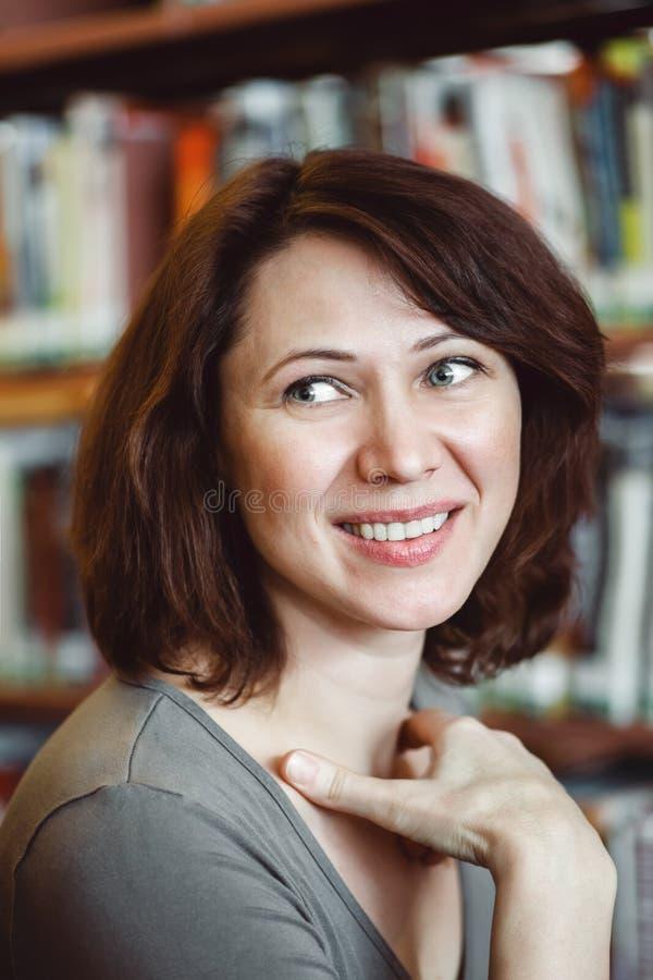 Close-upportret van glimlachende middenleeftijds rijpe studente in bibliotheek weg het kijken, het beroep van de leraarsbibliothe stock foto's