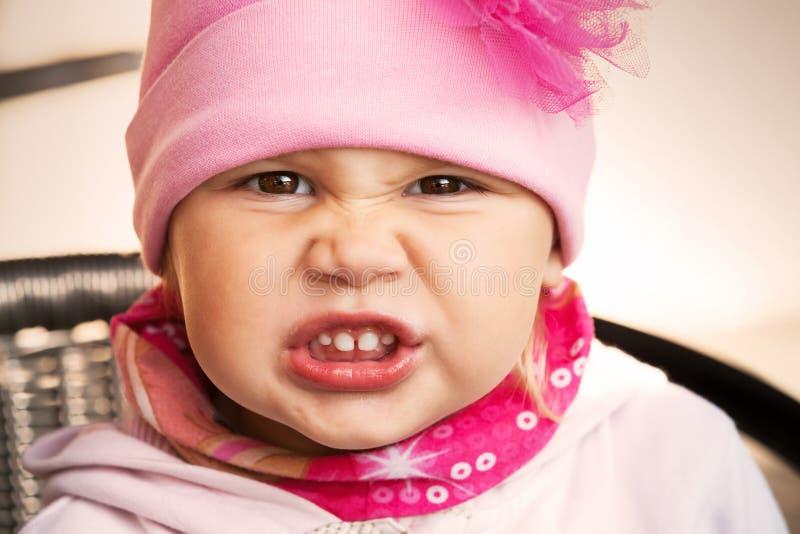 Close-upportret van grappig boos babymeisje stock afbeelding