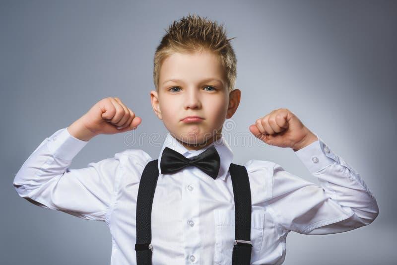 Close-upportret van Grappig Weinig kind het tonen van zijn spieren van handbicepsen Sterk ernstig jong geitje die zijn spieren va royalty-vrije stock foto's