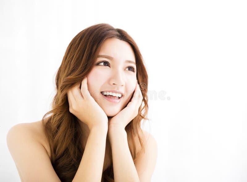 Close-upportret van het aantrekkelijke jonge vrouw glimlachen en het kijken stock afbeelding