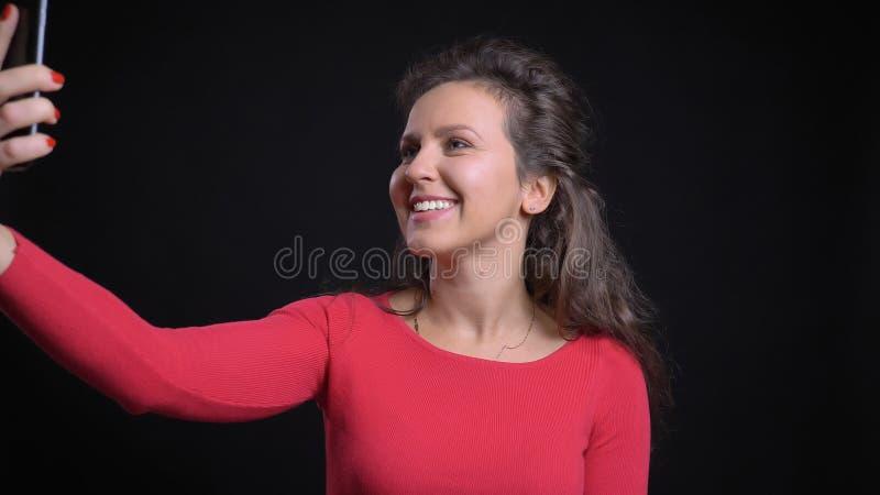 Close-upportret van het aantrekkelijke Kaukasische nemen op middelbare leeftijd selfies op de telefoon en het glimlachen voor de  stock foto