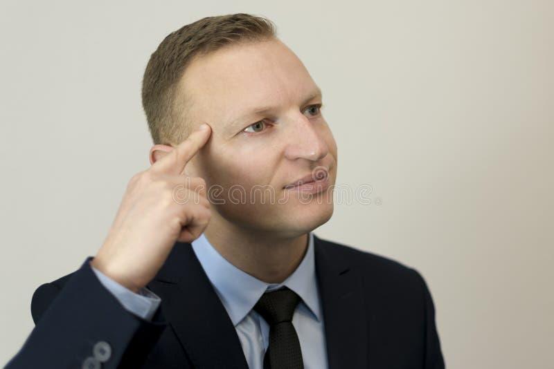 Close-upportret van het bedrijfsmens gesturing met zijn vinger tegen zijn tempel stock foto's