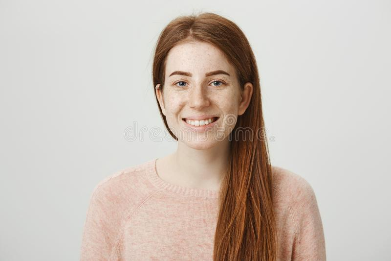 Close-upportret van het charmeren van Europees gembermeisje die ruim en positieve emoties glimlachen uitdrukken terwijl over het  royalty-vrije stock foto's