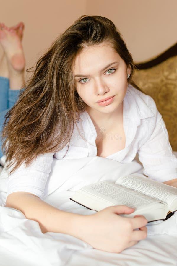 Close-upportret van het charmeren van jonge zoete donkerbruine vrouw in wit overhemd die op bed liggen die interessant boek lezen royalty-vrije stock fotografie