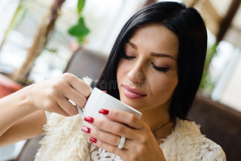 Close-upportret van het drinken van koffie of thee mooie sexy donkerbruin meisjes jonge vrouw die pret hebben die zacht gesloten  royalty-vrije stock foto