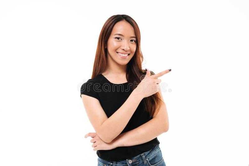 Close-upportret van het gelukkige jonge Aziatische meisje richten met vinger stock afbeelding