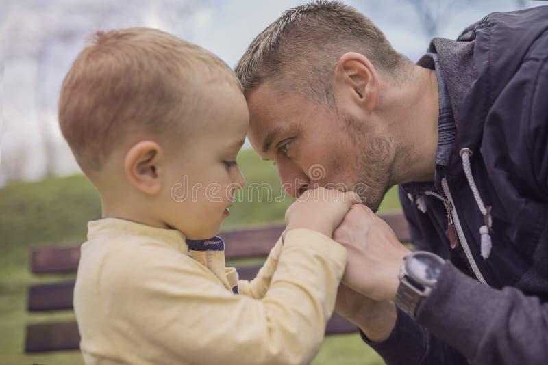 Close-upportret van het gelukkige vader en zoons spelen op speelplaats stock foto