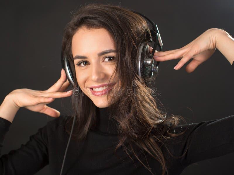 Close-upportret van het jonge mooie donkerbruine vrouw luisteren aan muziek en het houden van hoofdtelefoons over donkere grijze  royalty-vrije stock afbeelding