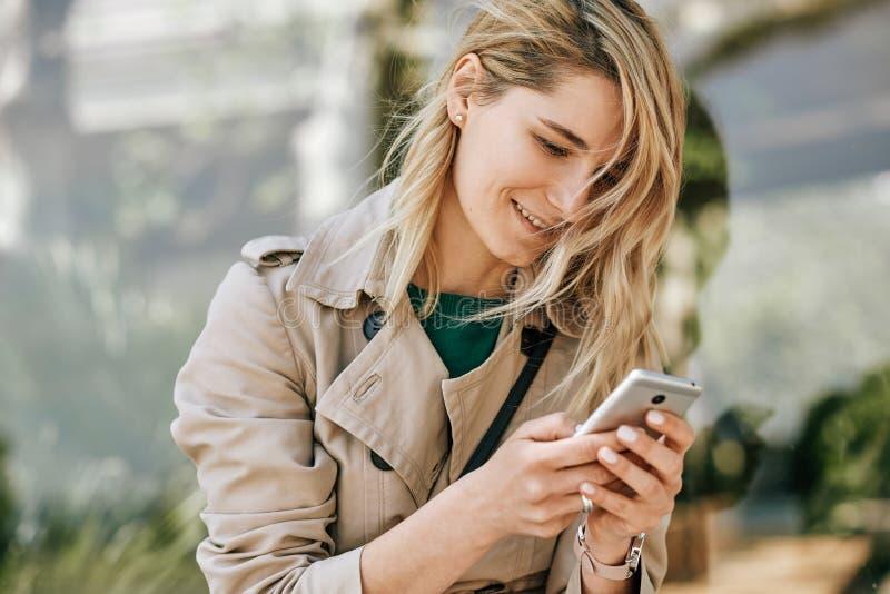 Close-upportret van het jonge mooie vrouw glimlachen en het schrijven berichten op smartphone, zitten openlucht in de stad bij zo royalty-vrije stock afbeeldingen
