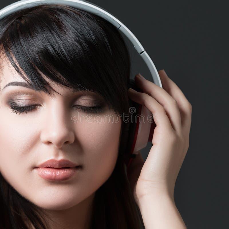 Close-upportret van het jonge vrouw luisteren aan muziek stock foto