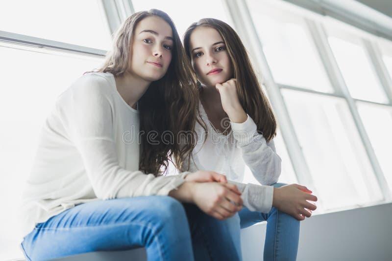 Close-upportret van het koesteren van 2 mooie jonge vrouwen die pret hebben stock afbeeldingen