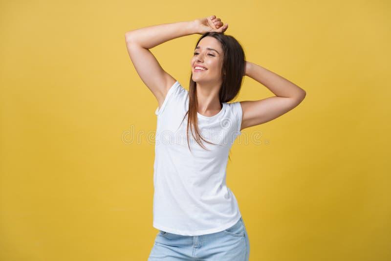 Close-upportret van het leuke jonge vrouw ontspannen met hand achter hoofd Geïsoleerd over gele achtergrond stock foto's